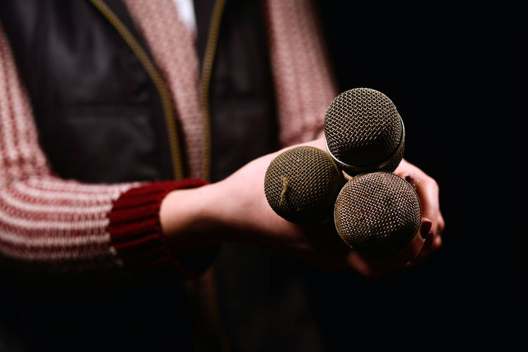 Close-up of woman holding microphones