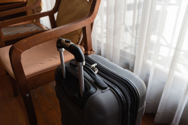High angle view of luggage by empty chair at home