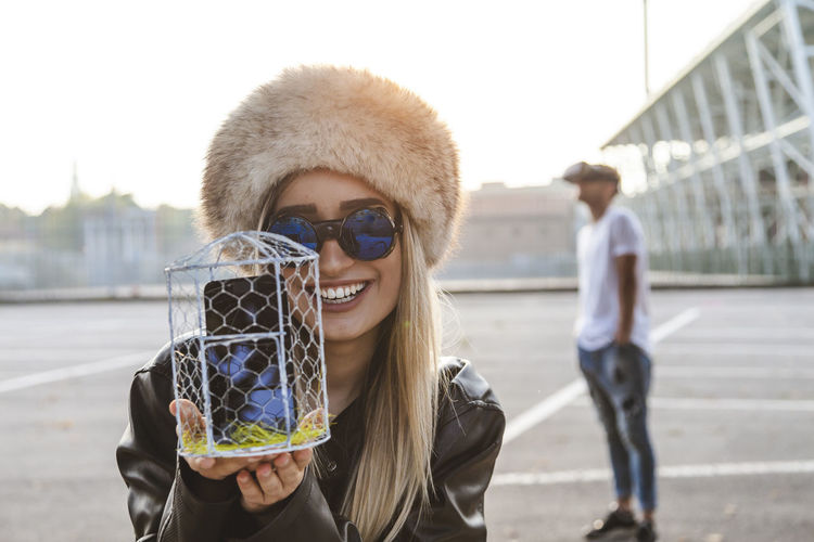 Portrait of woman showing smart phone in container