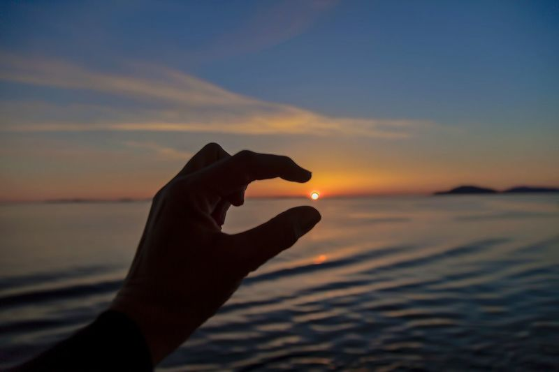 Cropped hand gesturing at sea against sky during sunset