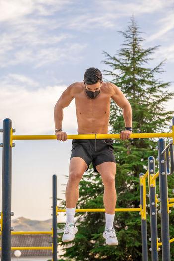 Full length of shirtless man against railing