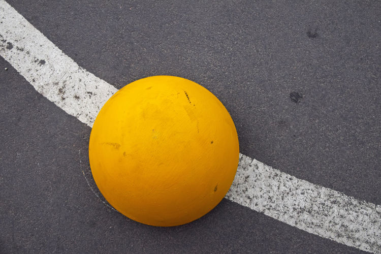 High angle view of sphere shape parking stopper on road