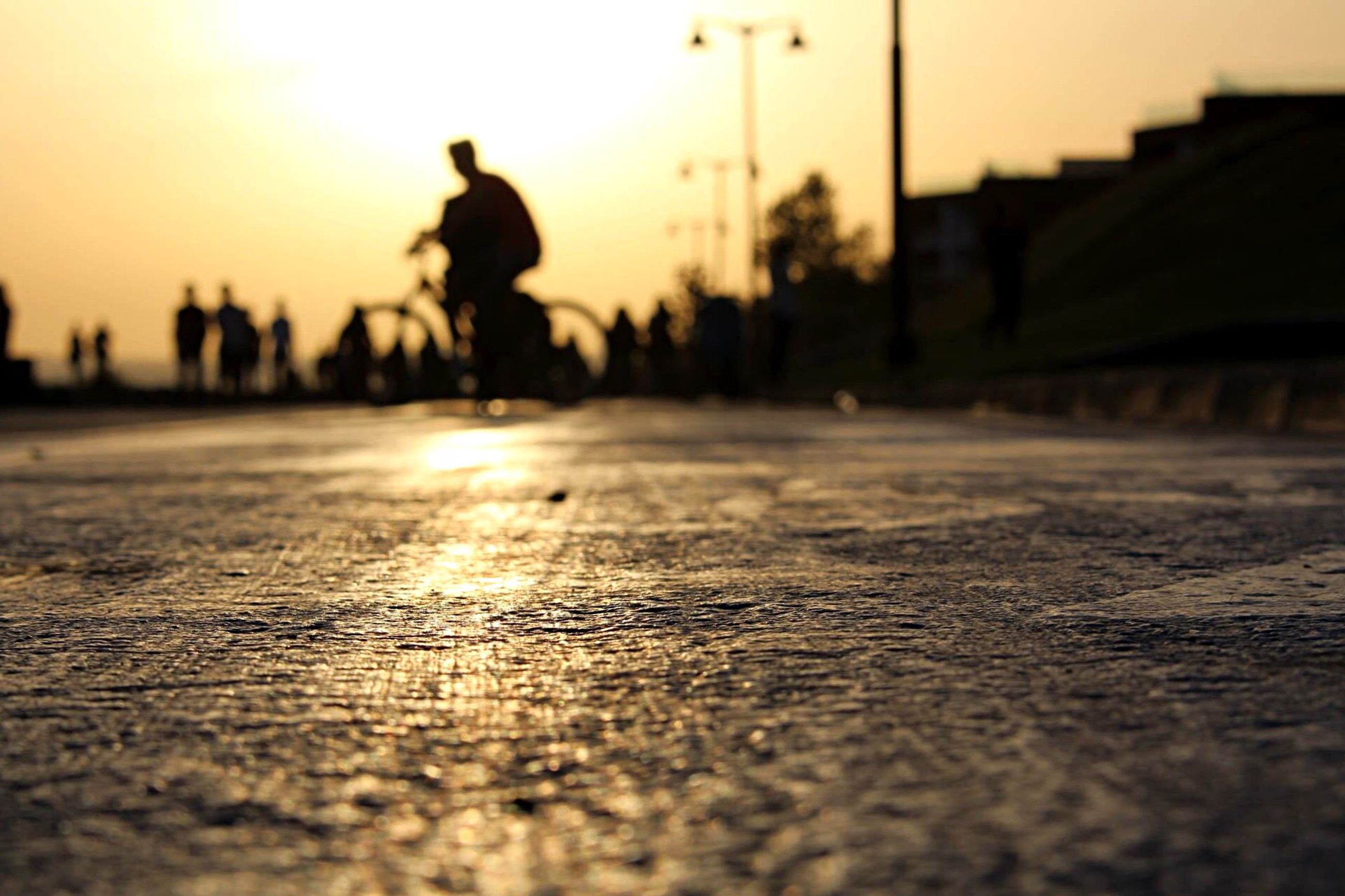 sunset, silhouette, surface level, selective focus, sky, street, walking, focus on foreground, sunlight, road, outdoors, leisure activity, outline, lifestyles, men, incidental people, nature, shadow, orange color