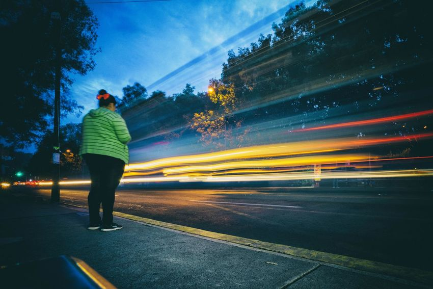 A woman waits for public transport in a downtown street of the city. HUAWEI Photo Award: After Dark Architecture Blurred Motion City Full Length Illuminated Light Trail Long Exposure Mode Of Transportation Motion Nature Night One Person Outdoors Rear View Road Sky Speed Street Transportation Tree