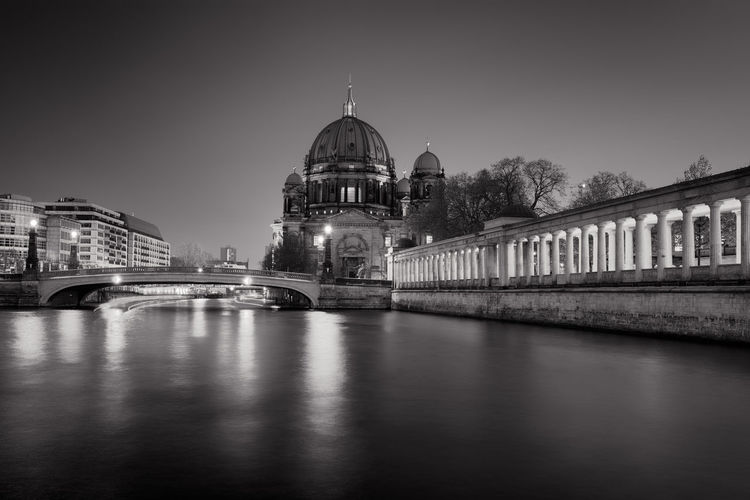 Illuminated river by berlin cathedral against clear sky during sunset