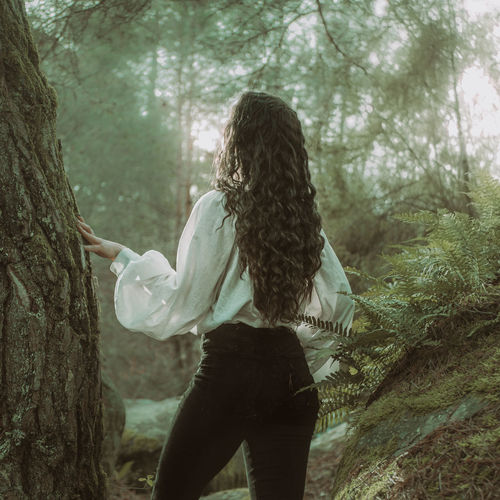 Rear view of woman standing in forest