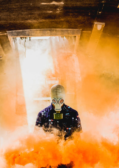 Teenage boy wearing mask amidst smoke