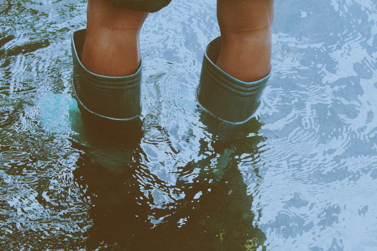 Low section of person wearing rubber boots while standing in water