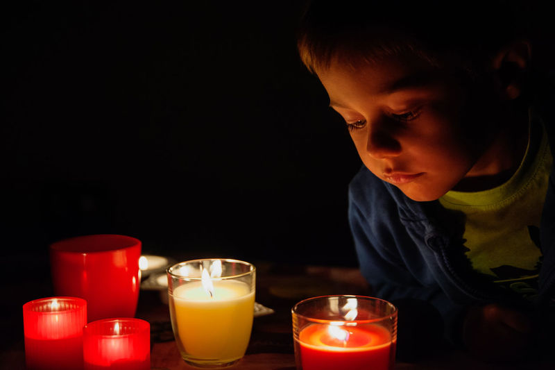 Close-up of boy looking at candles
