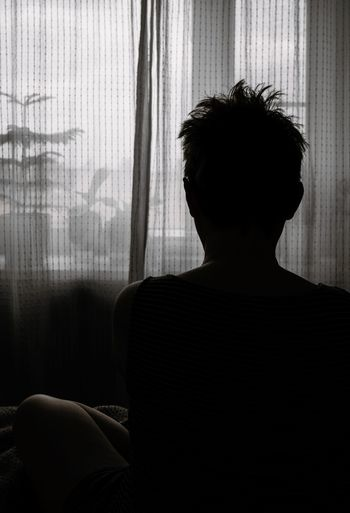 Rear of woman sitting in darkroom at home