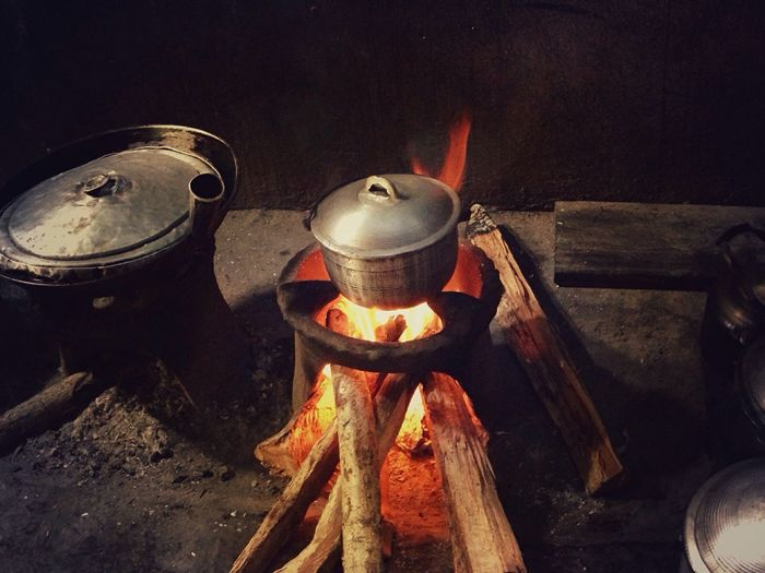 High angle view of cooking rice in container on firewood stove in kitchen