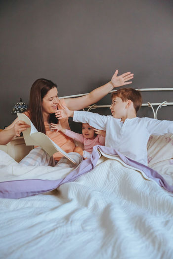 Close-Up Of Mother Telling Bed Time Story To Children On Bed At Home