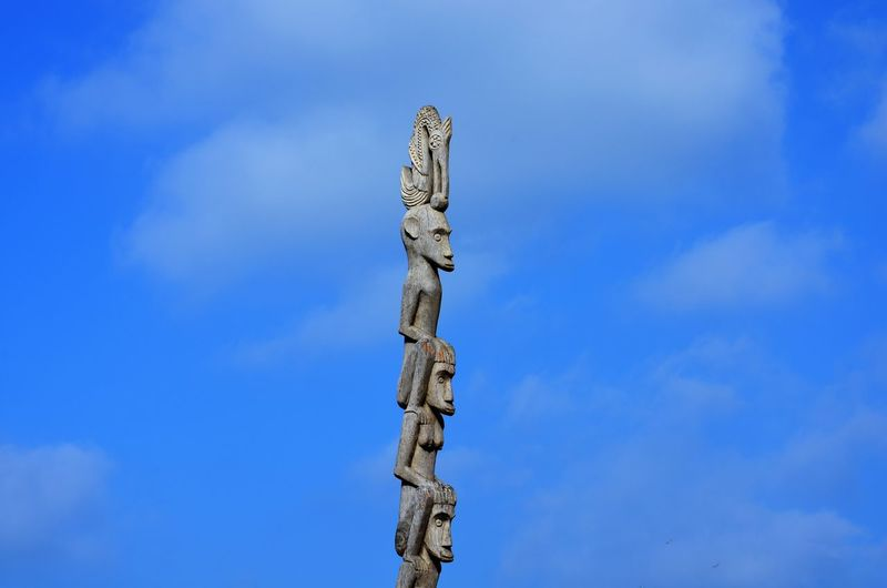 Low angle view of cross sculpture against blue sky