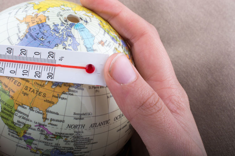 Close-up of hand with thermometer and globe
