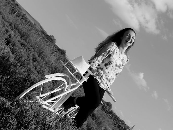 Low angle view of smiling woman standing by bicycle against sky