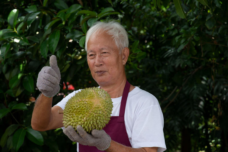 Smiling man showing thumbs up while holding durian
