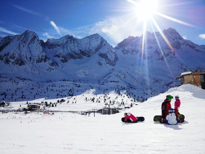 Father With Children On Snowcapped Mountain
