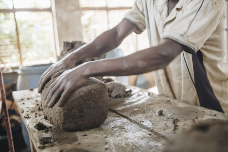 Midsection of worker kneading clay at table in workshop