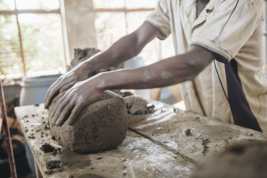 Africa African Business Ceramics Clay Clay Work Close-up Day Factory Hand Work Hands Human Hand Indoors  Manual Worker Manufacturing Motion Blur Occupation One Person Pottery Raw Material Sculpting Social Business Table Working Workshop
