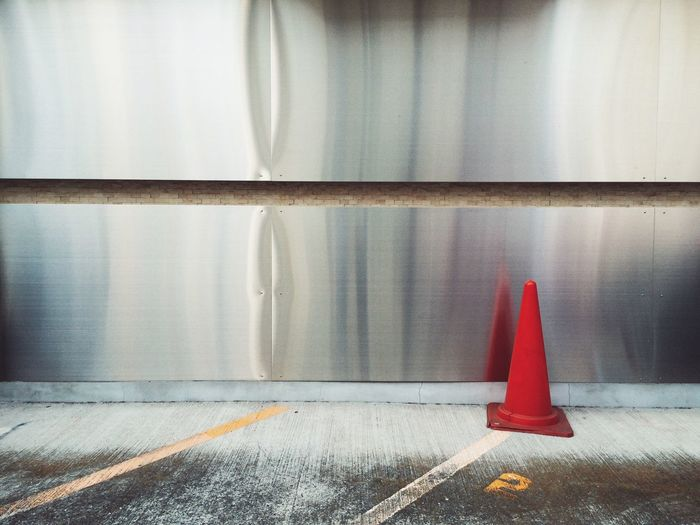 Red traffic cone by metal on road