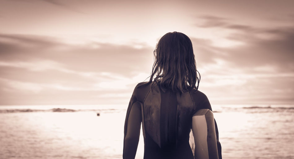 Rear view of girl against sea and sky
