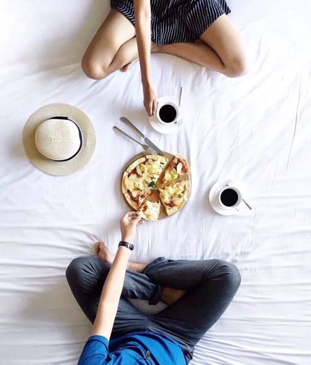Directly above shot of man and woman with pizza and coffee cups on bed