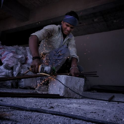 Worker drilling metal at workshop