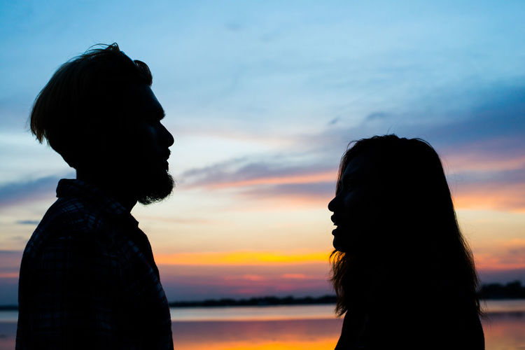 Silhouette man and woman against sky during sunset