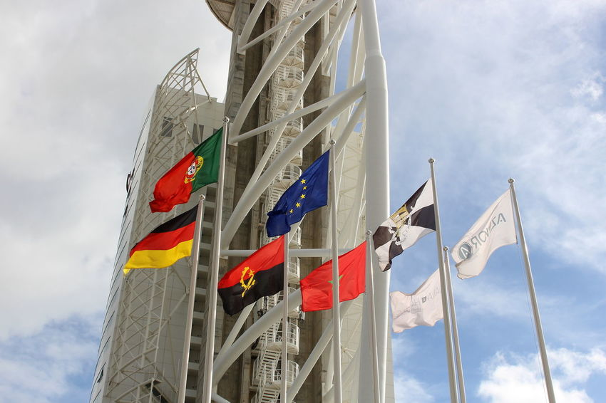 Cloud - Sky Flag Outdoors Low Angle View No People Day Flags Vasco Da Gama Tower Torre Vasco Da Gama Adapted To The City Architecture Business Finance And Industry Tower