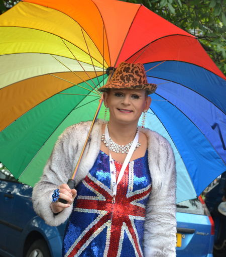 Costume Day Fancy Dress Front View Gay Pride Parade Happiness Leisure Activity Lifestyles Looking At Camera Multi Colored One Person One Young Woman Only Outdoors Patriotism People Portrait Rainbow Colors Rainbow Umbrella Raining Real People Smiling Standing Union Jack Young Adult Young Women