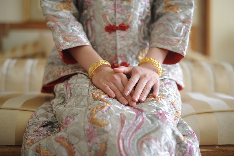 Midsection of woman in traditional clothing sitting on sofa