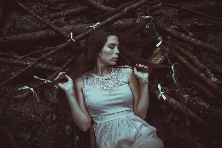 Woman sleeping on branch at forest