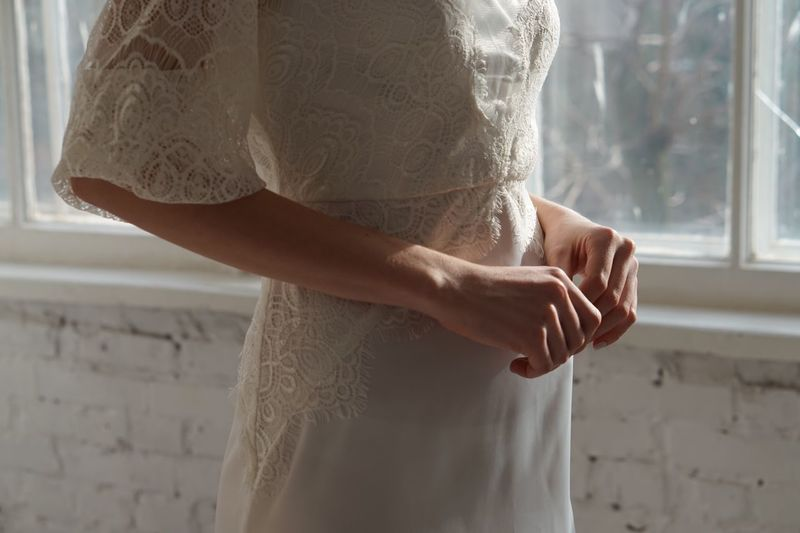 Midsection of bride standing by window at home