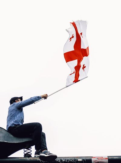 Low angle view of man holding flag against clear sky