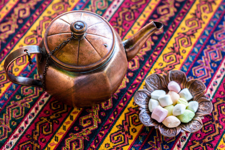 Close-Up Of Tea Kettle And Candies In Bowl On Table
