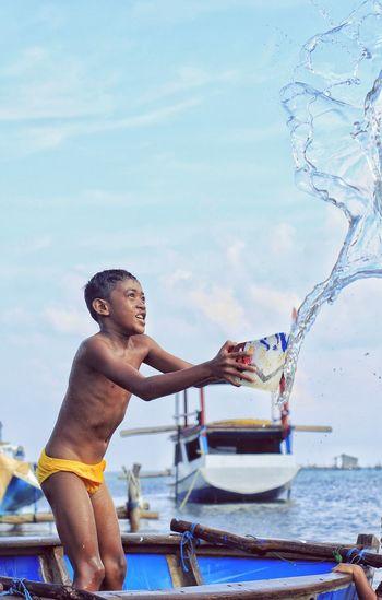 Full length of shirtless boy in water against sky