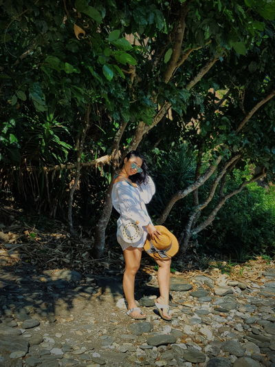beach life. Tree Full Length Water Spraying Plant Blooming Sun Hat Bikini Bikini Bottom Bikini Top Swimwear Sunbathing Beach Holiday Straw Hat Suntan Lotion