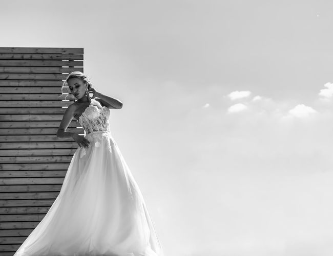 Low angle view of woman standing against sky