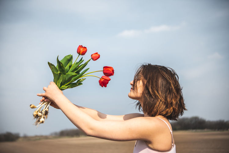 Tulips and her One Person Holding Plant Nature Land Day Outdoors Hairstyle Nature Natural Natural Beauty Natural Light Girl Brunette One Girl Only One Girl Tulip Tulips Bulb Bulbs Freshness Open Space Copy Space Copyspace Red Red Color Field Fields Meadow Flower Flowers Flora Floral