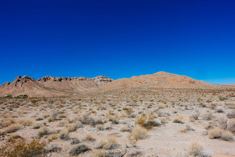 Scenic view of mojave desert against clear blue sky