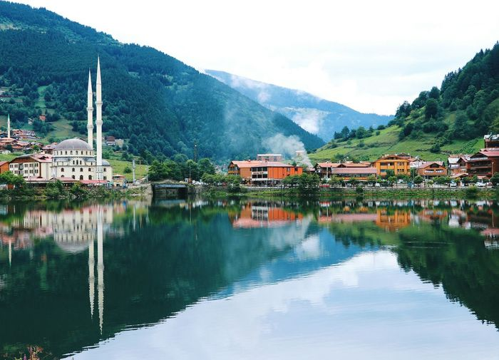 Mountains and buildings reflecting on lake in town