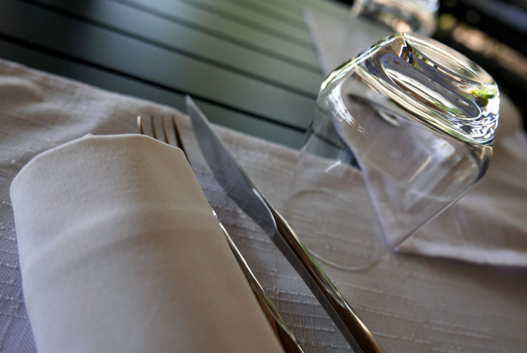 High angle view of napkin and silverware by glass on table at restaurant