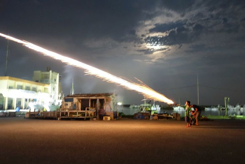 My oldest shooting a Roman candle last night during Obon. ISO3200, 1/4, F1.8