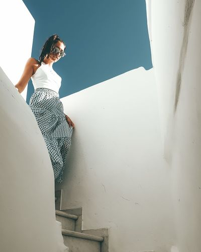 Young woman moving down on staircase against wall