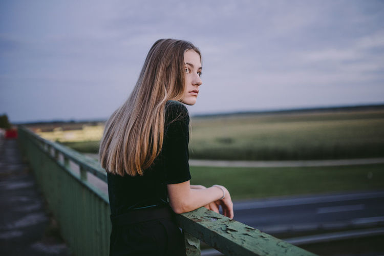 Side view of young woman standing by railing against sky