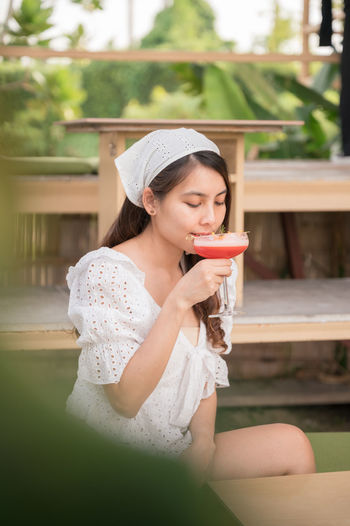 Beautiful young woman drinking glass while sitting outdoors