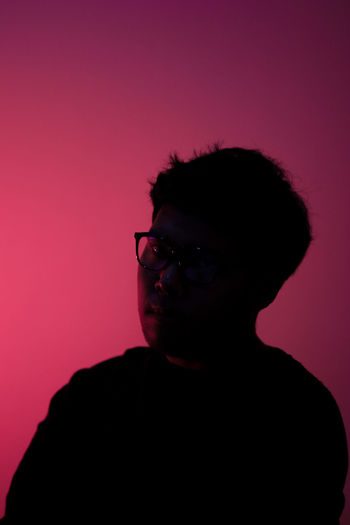 Portrait of young man against pink background