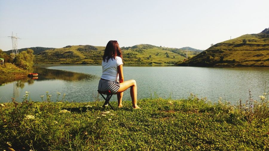 Solitary EyeEm Selects Water Young Women Full Length Women Sitting Lake Summer Clear Sky Relaxation Rear View