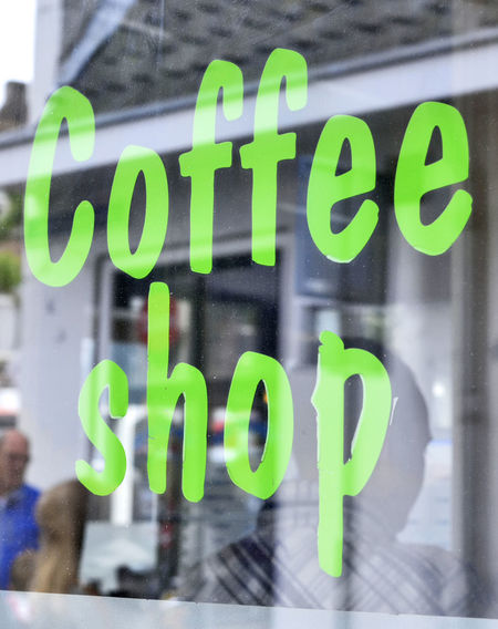 Coffeeshop sign at a shop window with selective focus. Amsterdam Coffee Shop Drugs Architecture Business Capital Letter Close-up Coffee Shop Scene Coffees Coffeeshop Coffeeshops  Communication Drug Abuse Focus On Foreground Green Color Information Joint Marihuana Message No People Outdoors Sign Text Western Script Window