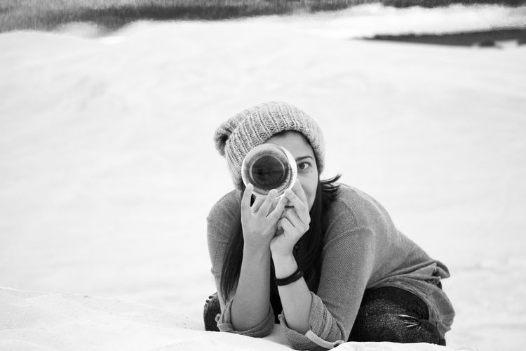 Portrait of woman holding crystal ball while sitting on snow covered land